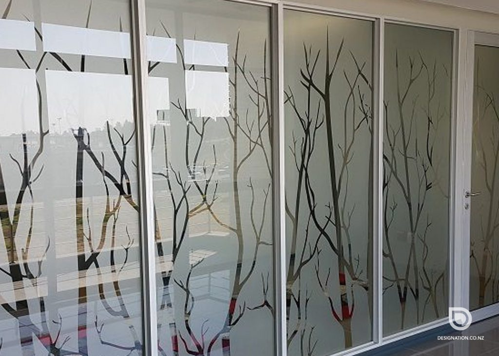 Cut vinyl window frosting in the shape of trees